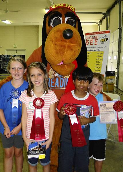Winners from the third and fourth grade category at the Literary Spelling Bee pose with Tales, the Harford County Public Library mascot, at the Harford County Farm Fair. Pictured, from left, are: Lizzy Kelly, first; and Elysa Puglionesi, Aman Tripatchi and Jeremy Jestel, who tied for second.