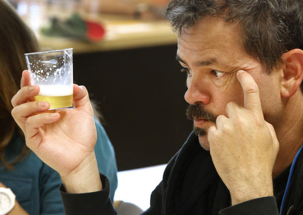 Steve Gonzalez, a judge for the California State Fair Commercial Craft Brew Competition, checks the color and clarity of a Kolsch beer during the judging in West Sacramento.