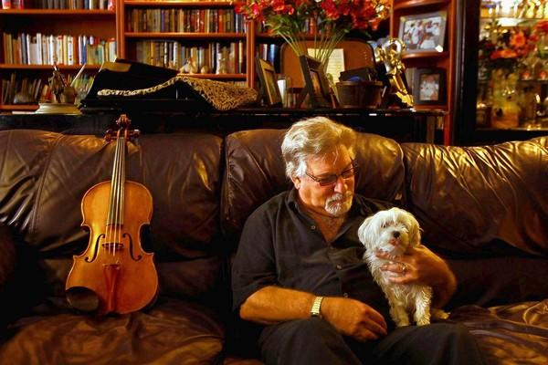 Former Los Angeles Philharmonic violist Jerry Epstein, 66, reclines with his dog Sadie, seated next to an idle viola in his West Hollywood home. Epstein's playing led to three rotator-cuff surgeries, and he can no longer lift his arm to play his viola. Epstein played for the Los Angeles Philharmonic for 43 years.