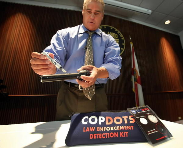 Shawn Andreas, President of CopDots, DNA For Your Property demonstrates how you apply the micro dots to your property Thursday, August 1, 2013. The Orlando Police Department will begin to utilize a new technology to combat property crimes.