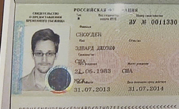Russian lawyer Anatoly Kucherena holds a temporary document that allows Edward Snowden to cross the border into Russia at Sheremetyevo airport outside Moscow. Snowden, who leaked secrets from the National Security Agency, has received asylum in Russia for one year and left the transit zone of Moscow's airport, his lawyer said Thursday.
