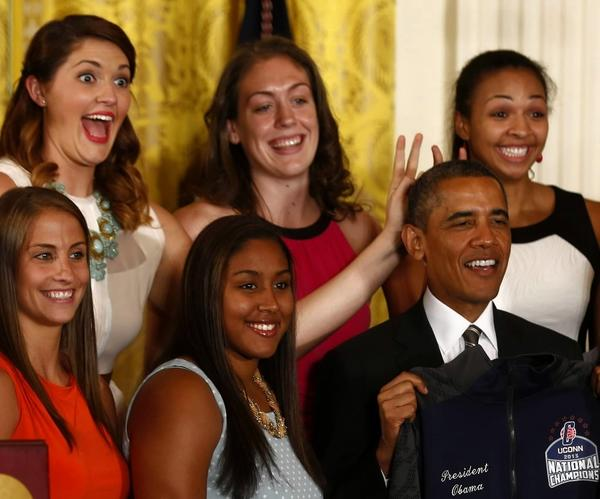 Stefanie Dolson (top left) and Khia Stokes (top right), members of the national champion UConn women's basketball team, put bunny ears over President Barack Obama during a ceremony to honor the team in the East Room at the White House in Washington on Wednesday.