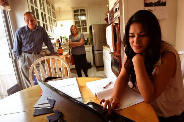Genesis Tenorio, right, moved back in with her parents in El Monte to save money as she applies for law school. Above, she prepares for the Law School Admission Test as Jose Luis and Coco Tenorio look on.