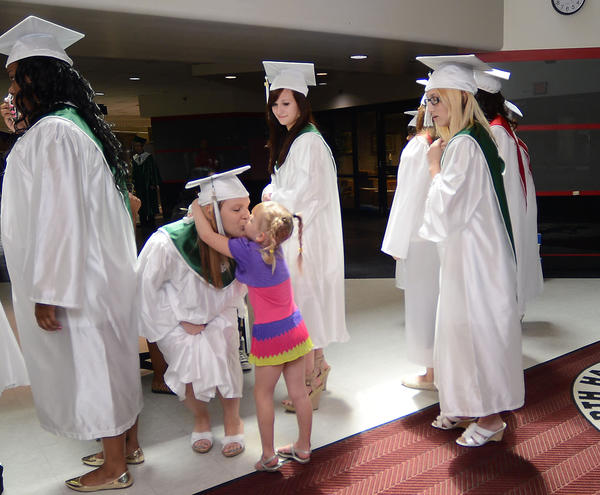 Graduate Morgan Hose gets a hug and kiss from her niece, Remy Wilson, 5, before the processional of the Washinton County Public Schools' Summer Learning Center Graduate Recognition Ceremony on Thursday.
