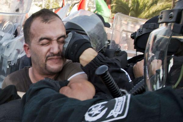 A protester is struck as he confronts Israeli police during a demonstration against government plans to resettle Bedouins.