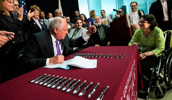 Gov. Pat Quinn gives a thumbs up to advocate Julie Falco, 48, after handing her a ceremonial pen and signing a bill legalizing medical marijuana Thursday at the University of Chicago Center for Care and Discovery. The law goes into effect Jan. 1.