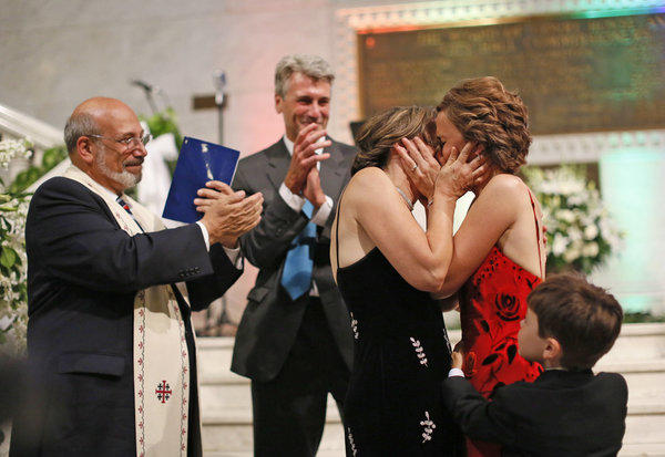 Margaret Miles and Cathy ten Broeke kiss after they were wed early Thursday on the steps of the rotunda at Minneapolis City Hall by the Rev. James Gertmenian, far left, and Mayor R. T. Rybak.