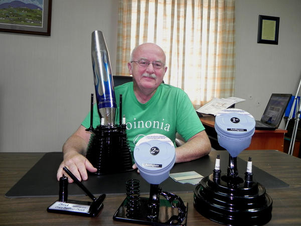 Pastor John Bayer shows some of the custom-built trophies made from engine parts that will be awarded at Saturday's first benefit car show at Grace Brethren Church in Chambersburg, Pa. The show is held in memory of Bayer's parents, John and Kathy Bayer.