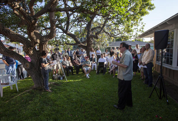 Costa Mesa Mayor Jim Righeimer talks to homeowners and members of the community at Carrie Renfro's Eastside home on Thursday about the issue of rehabilitation homes in Costa Mesa.