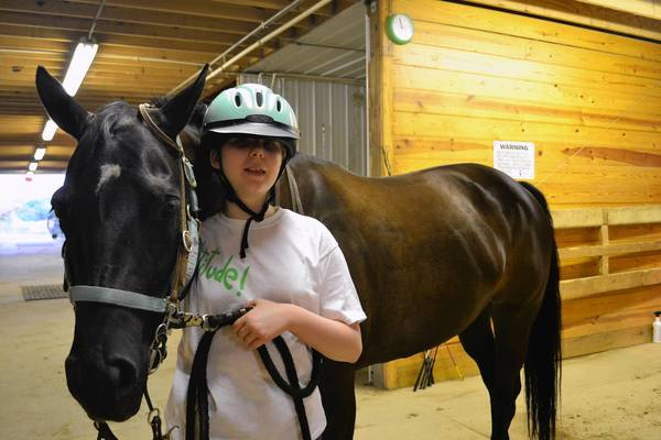 Rhiannon Huffman, 12, stands with her horse, Haley, at Partners for Progress, a therapeutic riding school in Wauconda.