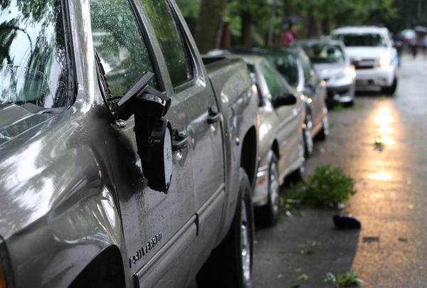 A Chevrolet truck with a dangling damaged mirror is one of at least 15 automobiles damaged by a truck dragging a tree limb down the 2200 block of North Burling Street in Chicago. Most of the damage consisted of damaged driver and passenger side mirrors, and scrapes.