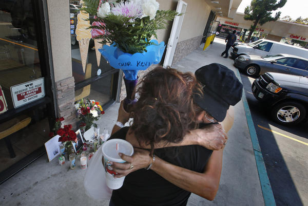 Two mourners embrace outside a Santa Ana shop where a police officer shot and killed a homeless man who frequently spent time in Costa Mesa.