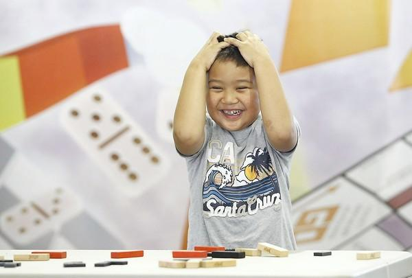 Luke Timbre reacts as his hard work comes tumbling down during the domino stacking contest in the Fun Zone game tent at the OC Fair on Wednesday.