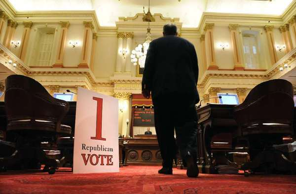 A senator checks a tote board in the California Capitol.
