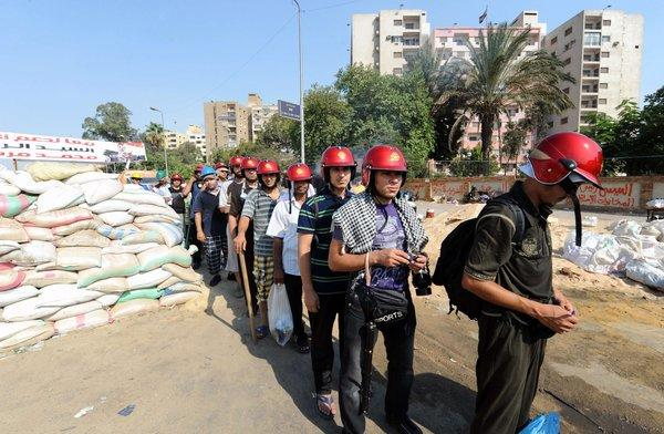 Egyptian supporters of deposed President Mohamed Morsi wear helmets and carry sticks during a march against the government.
