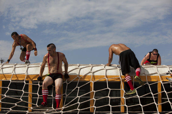 Runners scale an obstacle in the Concrete Hero race, benefiting AIDS Project L.A., in June.