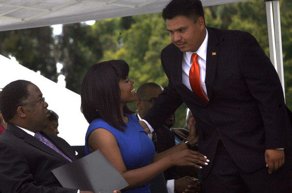 New Compton City Councilman Isaac Galvan, right, greets new Compton Mayor Aja Brown. The city has fired his aide, Angel Gonzalez, who had previous convictions for political misconduct.
