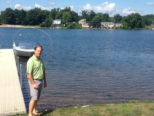 Michael Haines on the shore of Lake Congamond behind his West Suffield home. The shallow water to the right of the dock is where Haines found a broken grave marker.