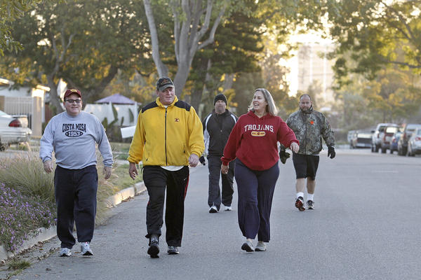 Costa Mesa Mayor Jim Righeimer, Mayor Pro Tem Steve Mensinger, former city employee Tim Sweet, local resident Kristen Kirk and Estancia High football coach Mike Bargas, from left to right, make their way through Arbor Street, headed to Canyon Community Park, during an early morning walk.