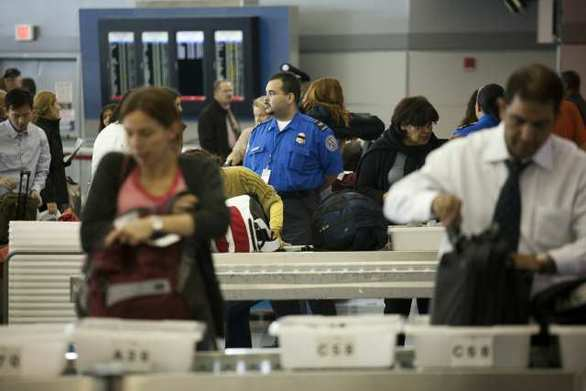 Travelers go through a TSA screening checkpoint at John F. Kennedy International Airport in New York.