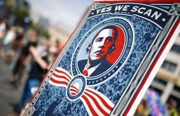 "A protester holds a placard showing U.S. President Barack Obama with the phrase ""Yes we scan"" during a demonstration against the National Security Agency (NSA) and in support of U.S. whistleblower Edward Snowden in Frankfurt, July 27, 2013."