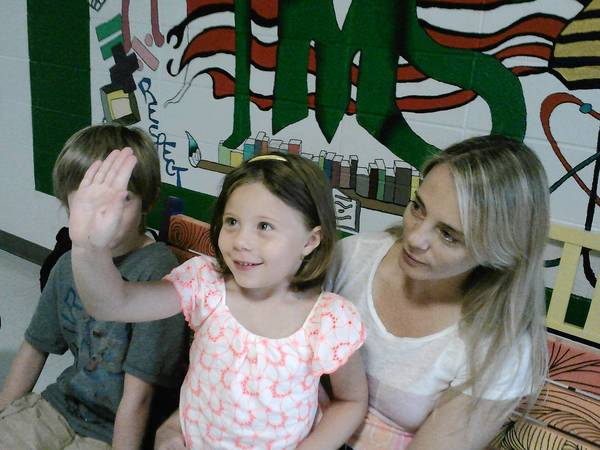 Lyla Shapiro, 5, with her mom, Doris, and 8-year-old brother, Will, holds up her hand to show her age when she starts kindergarten at Ivy Hill Elementary School this month.