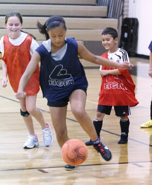 Samantha Frias, 12, turns and dribbles the ball in an indoor soccer match at the St. Francis High Soccer Camp on Monday. (Tim Berger/Staff Photographer)