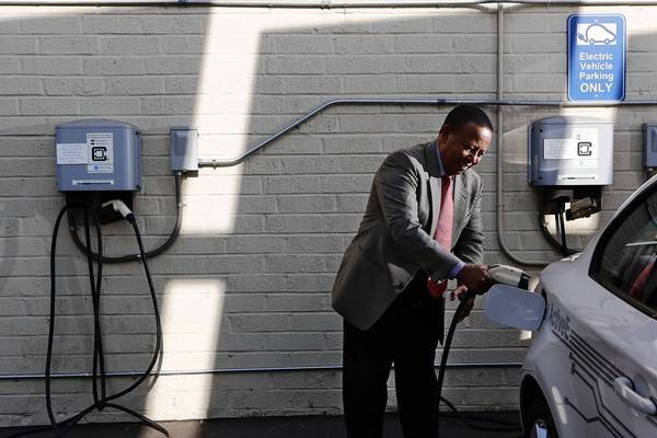 "As of July 20, there were 7,849 public and private non-residential charging stations in the United States, 1,579 of which were in California, according to the U.S. Department of Energy. Above, Yesewlik ""Leo"" Ayalew, finance chief of clean transportation consulting firm Calstart, plugs his electric car into a charging station at his office in Pasadena last week."