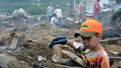 William Armstrong helps the Pyle family and neighbors clean up and salvage materials Friday from a barn fire at 174 Cross Road in Milford Township Wednesday. To see a photo gallery and video, visit dailyamerican.com.