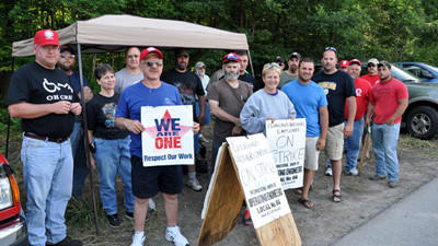 Union members stand together as a sign of solidarity on Friday while picketing outside the Cleveland Brothers Equipment Co. location along Industrial Park Road in Somerset. The workers have been picketing 24 hours a day for two weeks. A labor contract was finalized on Friday evening allowing employees to return to work on Monday, according to a company spokesman.