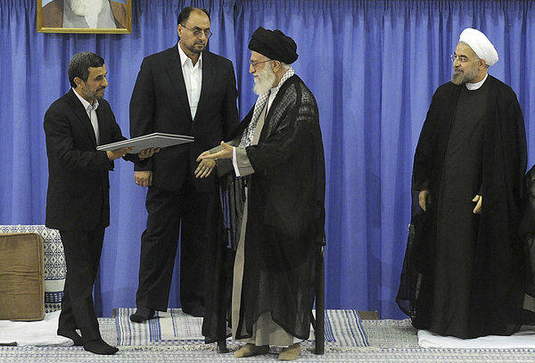 In this image released by the Iranian supreme leader's office, outgoing Iranian President Mahmoud Ahmadinejad, left, delivers the official seal of approval of Supreme Leader Ayatollah Ali Khamenei, center, to hand to President-elect Hasan Rouhani, right, in an official endorsement ceremony, in Tehran on Saturday. An member of the supreme leader's office stands at second left.