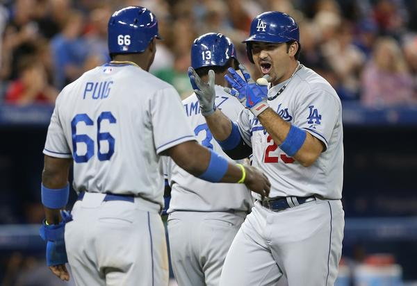 Adrian Gonzalez, right, is congratulated by Yasiel Puig after hitting a three-run home run during the eighth inning of the Dodgers' 10-9 victory over the Toronto Blue Jays on Tuesday.