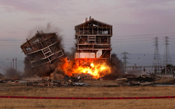 One tower falls as explosives that will bring down the other are detonated at an old Pacific Power and Electric power plant in Bakersfield. A man watching the demolition from 1,000 feet away was struck by flying debris and lost a leg, and others suffered injuries as well.