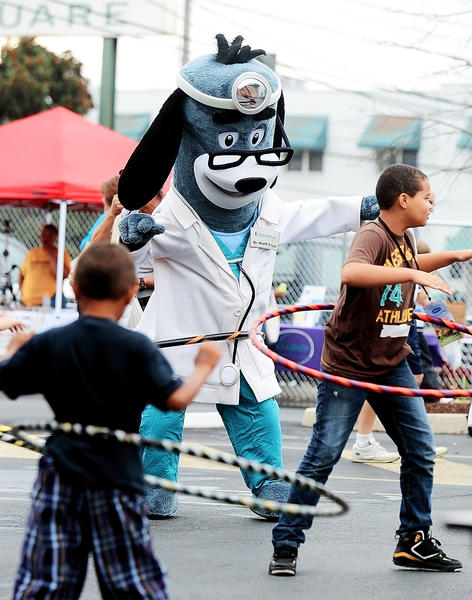 Dr. Health E. Hound and Jordan Meade hula hoop at the Walnut Street Community Health Fair on Saturday.