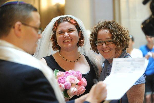 Rabbi Reuben Zellman of San Francisco reads the marriage license after marrying Marree, center, and Kate Burch, of Berkeley at San Francisco City Hall. They were one of many couples getting married after the U.S. 9th Circuit Court of Appeals lifted the stay on gay marriage in California.