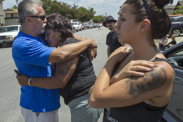 Carlos Gutierrez, left, hugs Roseanne Maestas, as Amanda Peukert, right, looks on at the site of an officer involved shooting near Sun View Elementary School in Huntington Beach on Saturday. Maestas believes her nephew Eric Marquez was shot and killed but an official identification has not yet been released.
