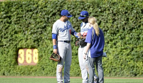Dodgers center fielder Andre Ethier, left, and team trainer Sue Falsone look at right fielder Yasiel Puig's left hand after he made a diving catch in the seventh inning of Saturday's win over the Chicago Cubs.
