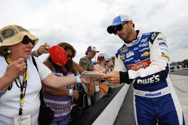 Jimmie Johnson, driver of the #48 Lowe's Planes Chevrolet, signs autographs during qualifying for the NASCAR Sprint Cup Series GoBowling.com 400 at Pocono Raceway on August 2, 2013 in Long Pond, Pennsylvania.