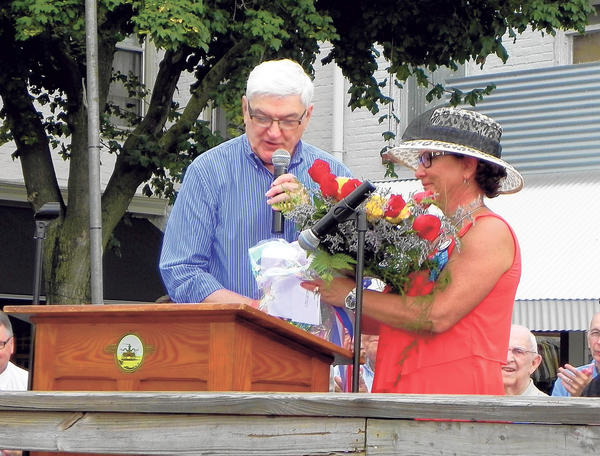 The Rev. Wayne Warren presents a bouquet of roses to Carol Christophel, the first female president of Greencastle-Antrim Old Home Week, on Saturday during the opening ceremony of the 38th triennial event on the square in Greencastle, Pa.