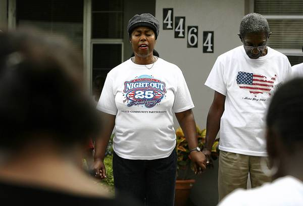 Residents of Richmond Heights hold hands in prayer during previous National Night Out.