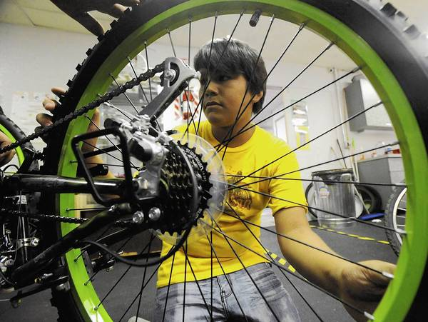 Luis Litardo, 11, of Allentown helps inspect tires on a refurbished bike at the Community Bike Works, which gets federal funding.