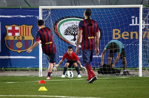 FC Barcelona's Lionel Messi, left, participates in a training session with Palestinian children at Dura stadium in the West Bank.