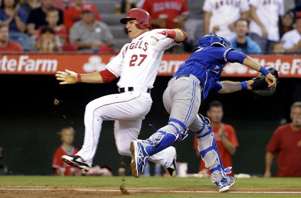 Blue Jays catcher J.P. Arencibia chases a wide throw to home as Angels center fielder Mike Trout scores in the fifth inning Saturday. Arencibia would then make a wild throw to second base, allowing Josh Hamilton and Howie Kendrick to score.