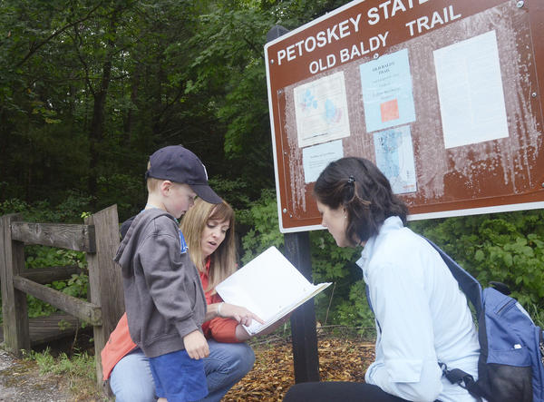 Outdoor education specialist Maureen Stine (center) points out to Sara Ward (right) and her son Anderson, 4, plant life to look for along the trail at Petoskey State Park. They were participating in a recent Getting Kids Outdoors in Emmet County summer nature workshop.