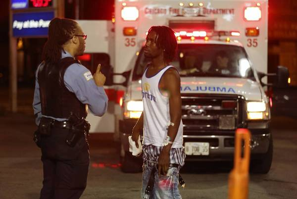 A Police officer talks with a man shot in his right hand at 47th and Michigan Ave. on Aug. 3.