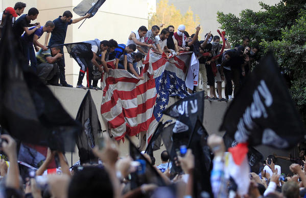 Protesters destroy an American flag pulled down from the U.S. embassy in Cairo on September 11, 2012.