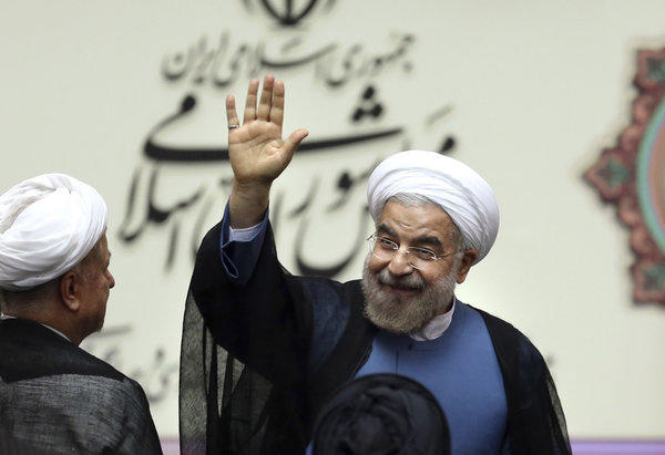 Iran's new President Hassan Rouhani greets the crowd after his swearing in at the parliament in Tehran on Sunday.