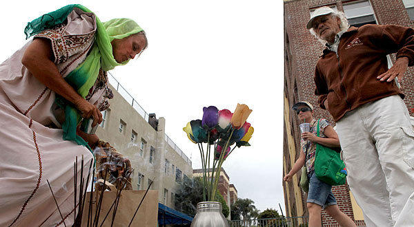 Lisa Green and Toneey Acevedo stop to place remembrances at a makeshift memorial on the Venice boardwalk.