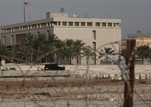 A Bahraini armored personnel vehicle and personnel reinforce U.S. Embassy security just outside a gate to the building, surrounded in barbed wire, in Manama, Bahrain.