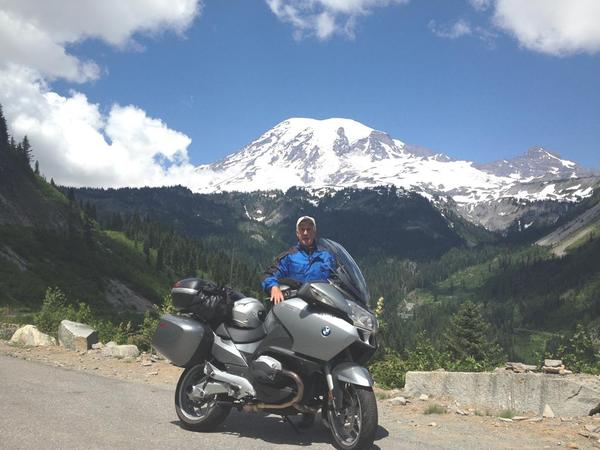 Randy Ward of State Line, Pa., poses in front of Mount Rainier in Washington, one of his many stops on a motorcycle ride through all 48 states.